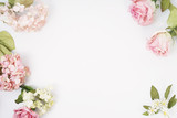 Fototapeta Kwiaty - Frame made of pink and beige roses, hydrangea, green leaves, branches on white background. Flat lay, top view. Wedding's background. Valentine's background with copy space.