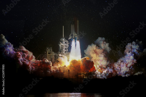 Fotografía Spaceship launch at night, landscape with colorful smoke clouds and galaxy background