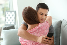 Young Cheater Texting Lover While Hugging His Girlfriend At Home