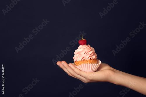Photo  Female hand holding delicious cupcake on dark background