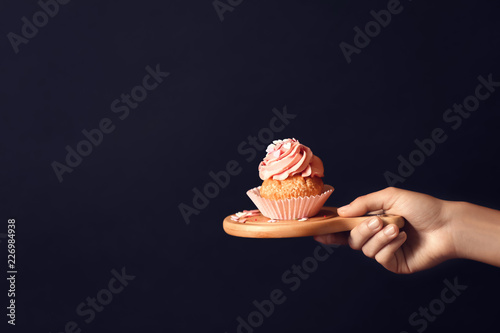 Photo  Female hand holding wooden board with delicious cupcake on dark background
