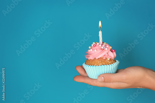 Female hand holding delicious birthday cupcake with burning candle on color back Wallpaper Mural