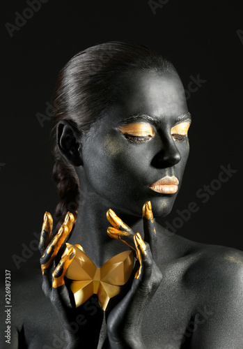 Obraz Beautiful woman with black and golden paint on her body against dark background - fototapety do salonu