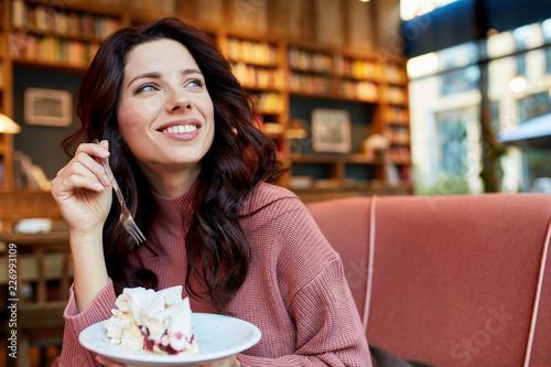 Fototapeta pretty woman eat a cake in a cafe. Pleasure time obraz