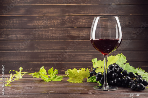 Fotobehang Alcohol wine glass and bunch of grapes on wooden table
