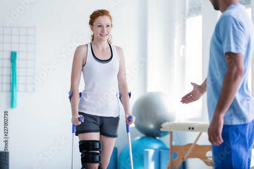 Leinwand Poster Woman walking with crutches during physiotherapy