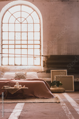 Papiers peints Akt Arch window in a wabi sabi bedroom interior with a bed and iron radiator. Real photo