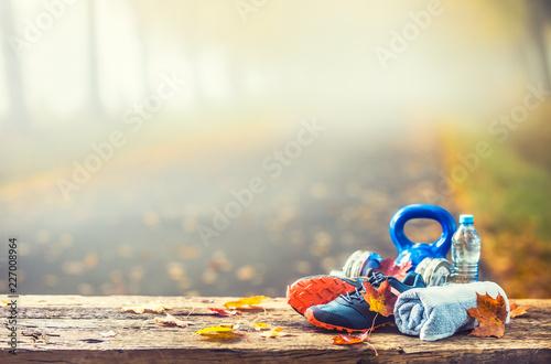 Niebieskie buty sportowe i woda ułożone na drewnianej desce.