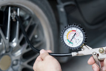 Close Up Mechanic Inflating Tire Hand Holding Gauge Pressure For Checking And Filling Air In Car Tire. Automobile Concept.