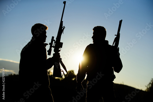 Foto op Plexiglas Jacht Hunting with partner provide greater measure safety fun and rewarding. Hunter friend enjoy leisure. Hunters friends gamekeepers with guns silhouette sky background. Hunters rifles nature environment