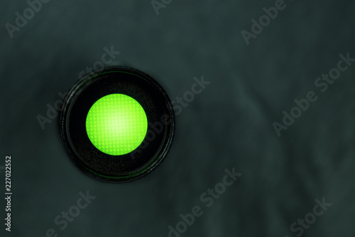 Fotografía  An overhead photo of a vibrant green button on a dark panel with copyspace