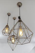 Retro Interior Copper Hanging Lamp With Orange Light Bulb.