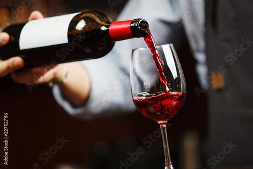 Carta da parati Waiter pouring red wine into wineglass