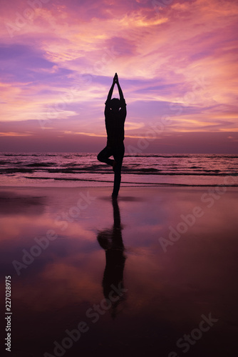 Silhouette of a young man meditating at sunset at beach