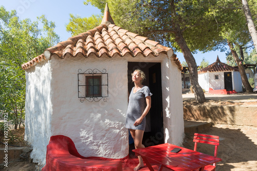 Photo  Woman enjoying refreshing and relaxing summer vacations in authentic vintage bungalow of camping village under mediterranean pine trees, Palau, Sardinia, Italy