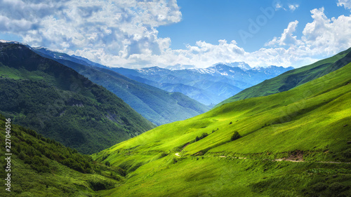 Foto auf Leinwand Gebirge Mountain green alpine valley. Bright Mountains landscape. Hills covered by green grass. Grassy highlands in Svaneti region of Georgia on summer sunny day. Amazing view on Caucasus nature