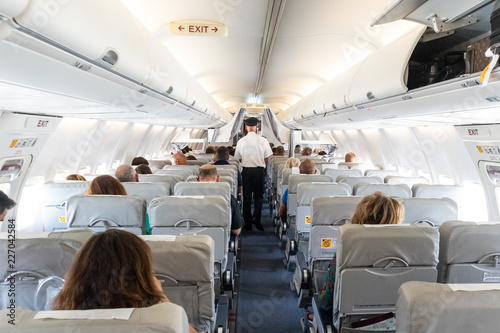 Tuinposter Interior of commercial airplane with unrecognizable passengers on their seats during flight. Steward in blue white uniform walking the aisle of commercial airplane.