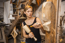 Sculptress Carving Wooden Figure In Workshop