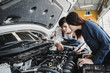 Reliable auto mechanic talking to a female customer the engine error in a modern automobile repair shop