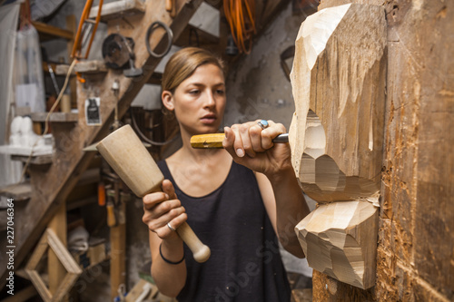 Sculptress carving wooden figure