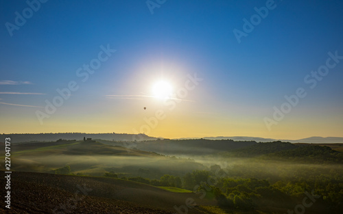 Deurstickers Toscane sunrise above tuscany landscape with hot air balloon