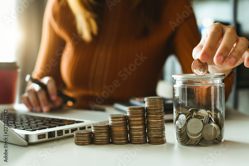 Fototapeta businessman holding coins putting in glass with using smartphone and calculator to calculate  concept saving money for finance accounting obraz