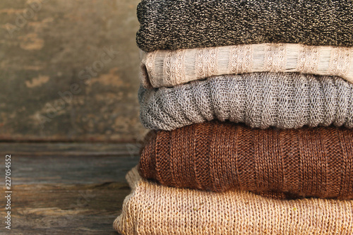 Fotografie, Obraz  Pile of colorful warm clothes on wooden background.