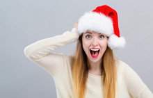 Young Woman With A Santa Hat Making A Mistake On A Gray Background