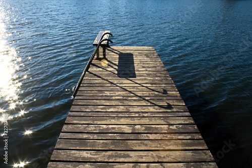 Beautiful wooden pier with bench and sun reflected on calm and blue water
