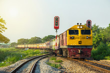 Procession Train Led By Yellow Diesel Electric Locomotives At Curve And Sail Through Rail Chopper With Traffic Light Before Entering Ratchaburi Station Of Thailand.