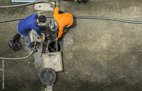 Obraz na plátně Pipe cleaning drainpipe by two workers to get rid of obstruction Passage of water in the rainy season in image bird eye view