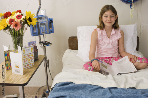 Fényképezés  Girl in hospital bed reading magazine at camera with get well soon cards