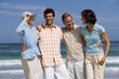 canvas print picture - Group of friends as couples on summer vacation standing on beach