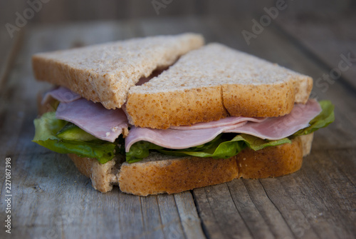 Club Sandwich with Ham and Vegetables. Rustic wooden background.