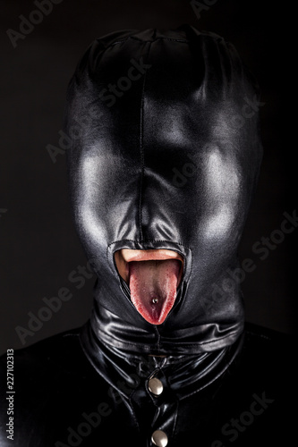 Fotografering  portrait of a woman with fully covered face behind a shiny rubber like head mask
