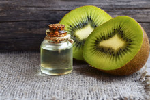Essential Kiwi Seed Oil In A Glass Jar With Fresh Halved Kiwifruit On Old Wooden Background.Aromatherapy,spa,beauty Treatment And Bodycare Concept.Selective Focus.