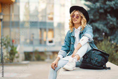 Stylish girl spent time in the city sitting near modern glass bu