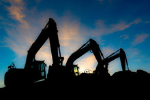 Silhouette Of Excavators On A Background Of Blue Sky