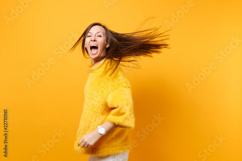 Foto  Overjoyed comic young girl in fur sweater white pants whirling fooling around in studio jumping with fluttering hair isolated on yellow background