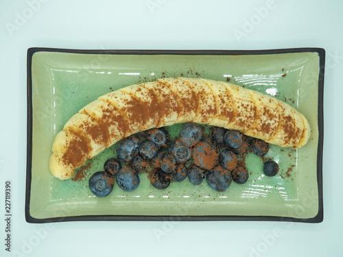 Fotografía  Postre de plátano con arándanos y cacao puro en polvo.