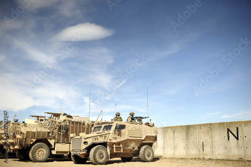 Fotografía Desert camouflage armoured vehicles at base behind concrete walls