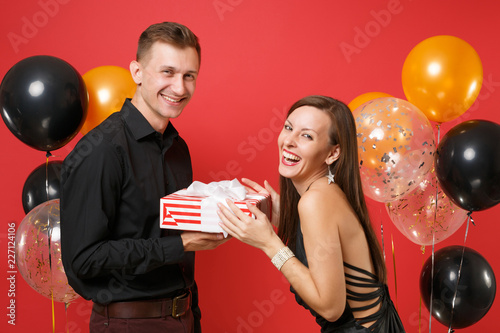young couple in black clothes hold gift box celebrating birthday holiday party isolated on bright red