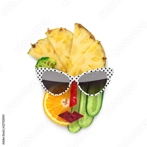 Tasty art / Creative concept photo of cubist style female face in sunglasses made of fruits and vegetables, on white background.