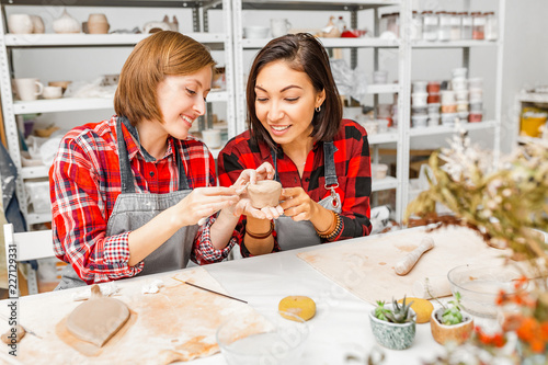 Young woman friends create clay and ceramic art dishes in pottery workshop