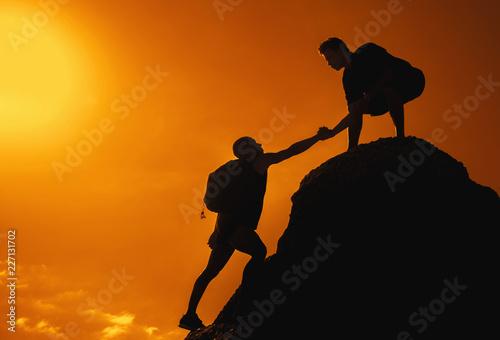 Photo Mann auf dem Gipfel reicht Freund die Hand