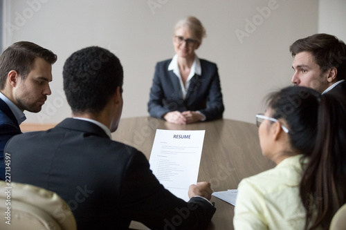 Fotografie, Obraz  Back view of millennial HR managers read middle aged female applicant resume con