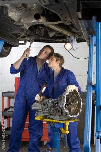Mechanics with car engine part in auto repair garage Canvas Print