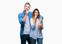 Young Couple In Love Over Isolated Background With Hand On Chin Thinking About Question, Pensive Expression. Smiling With Thoughtful Face. Doubt Concept.