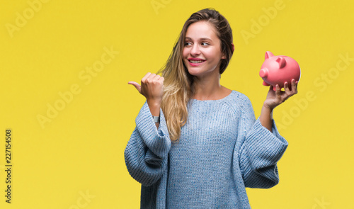 Fotografía  Young beautiful blonde woman holding piggy bank over isolated background pointin