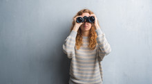 Young Redhead Woman Over Grey Grunge Wall Looking Through Binoculars With A Confident Expression On Smart Face Thinking Serious